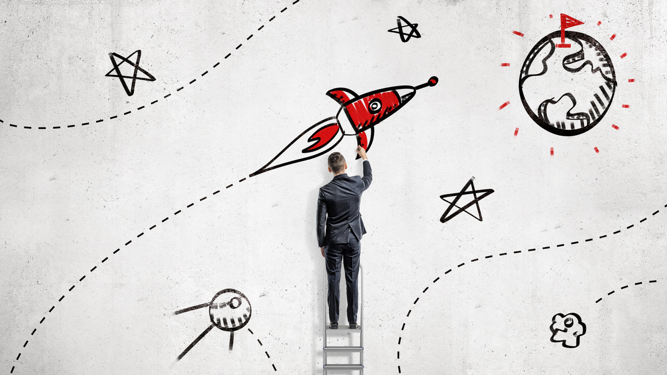 A businessman draws paints a rocket that will reach a goal set on a planet's surface. High aspirations. Business planning. Life and business goals.