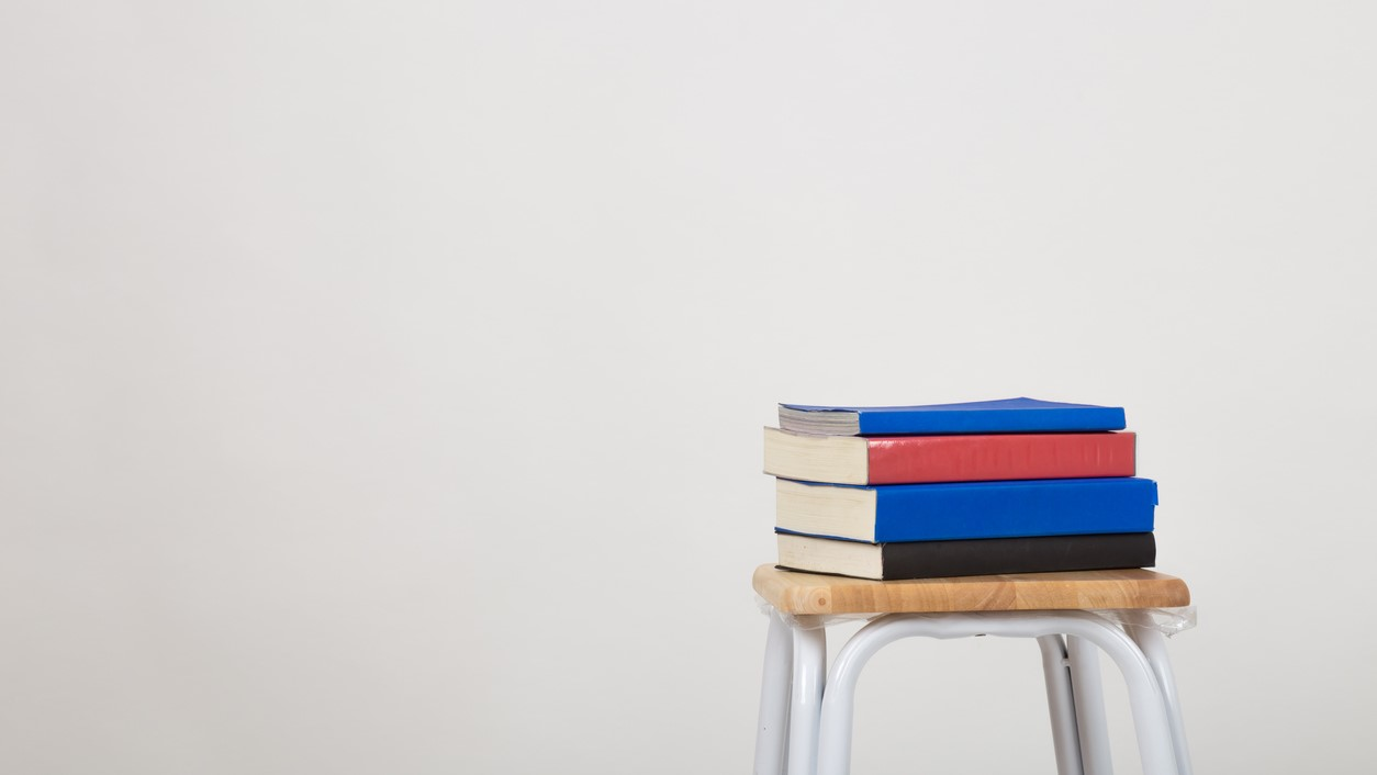 A stack of books on a chair. Isolated a white background.